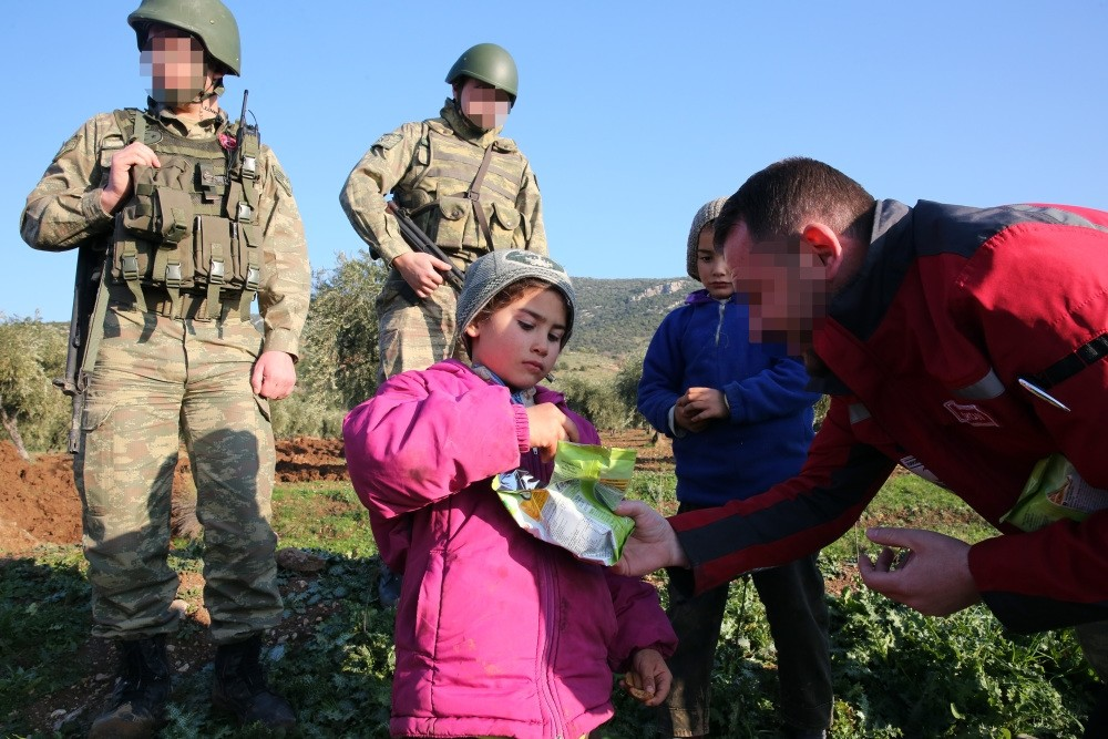 A Syrian child, who lives in village of the Sorke in northern Afrin, receives food aid from a Turkish soldier, Syria, Feb. 2.