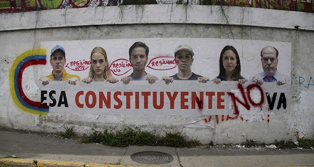 A poster that shows some of Venezuela's opposition leaders holding a sign with a message that reads in Spanish: That constituent assembly will not pass is displayed on a wall near Altamira Square in Caracas, Venezuela, Aug. 3, 2017. (AP Photo)