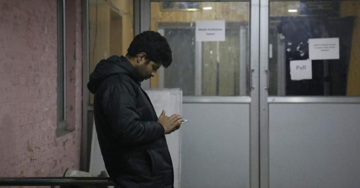 A man checks his cellphone outside a media facilitation center in Srinagar, Indian controlled Kashmir, Tuesday, Dec. 31, 2019 (AP Photo)