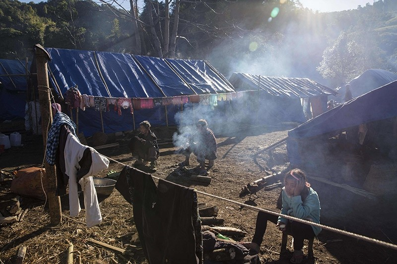 Refugees in front of their temporary shelter near Lung Byeng village, Waimaw township in Kachin state, Myanmar. Jan. 2017. (AFP File Photo)