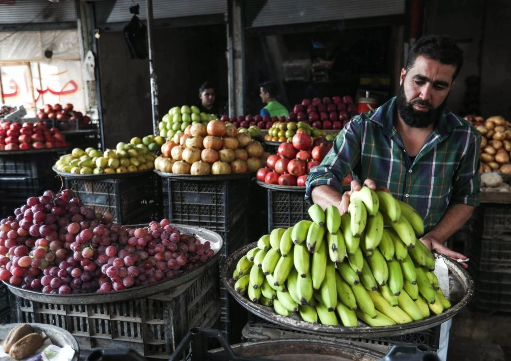 A Syrian fruit merchant organizes bananas outside his shop in the opposition-held town of Maaret al-Numan, just south of Idlib province, Sept. 27.