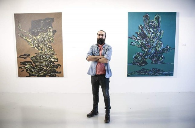 Adnan Jetto poses with some of his works at the exhibition. AA Photo