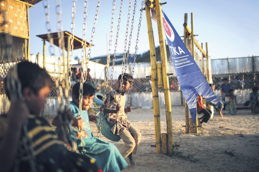 Rohingya refugee children sit on swings in a playground established by the Turkish Cooperation and Coordination Agency (Tu0130KA), Bangladesh, June 6.