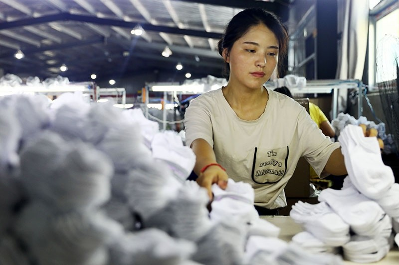 A woman works on socks that will be exported to the US at a factory in Huaibei in China's eastern Anhui province on Aug. 7, 2018. (AFP Photo)
