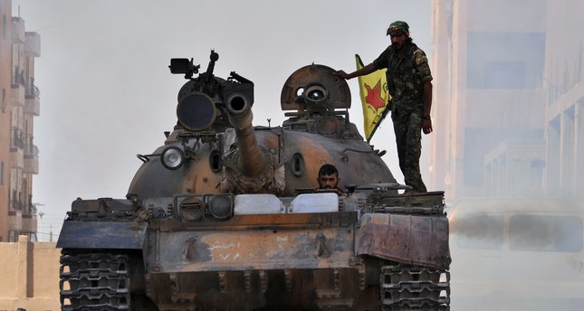 YPG militias drive a tank in the al-Zohour nieighbourhood of northeastern Syrian city of Hasakeh on August 2, 2015. (AFP PHOTO)