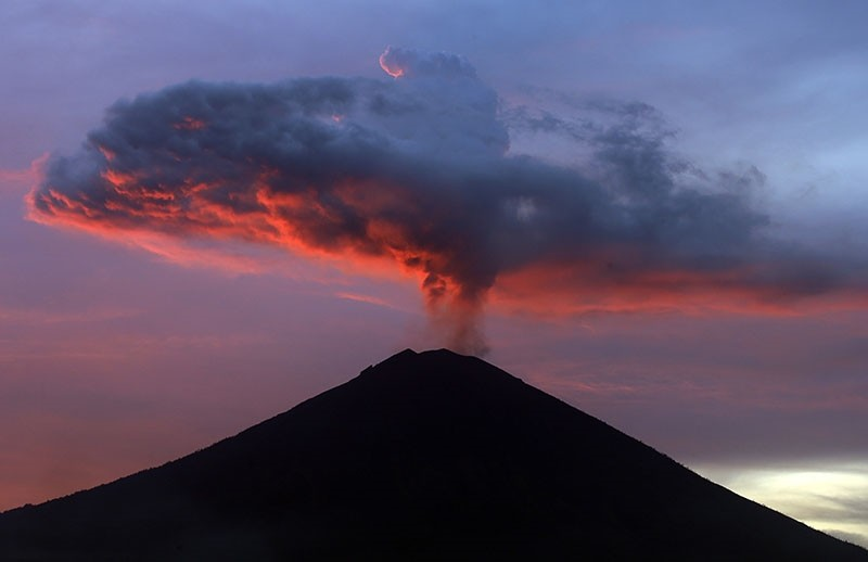 This file photo shows clouds of ash from Mount Agung volcano are lit with warm sunset light in Karangasem, Bali, Indonesia, on Nov. 30, 2017. (AP Photo)