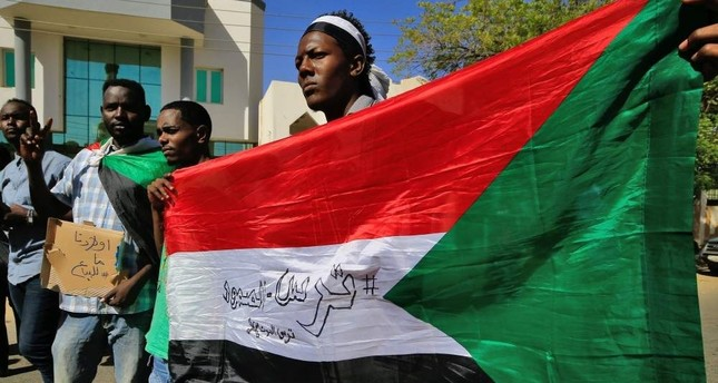 Sudanese demonstrators carry placards and wave their country's national flag as they gather to protest outside the Foreign Ministry, Khartoum, Jan. 28, 2020. AFP Photo
