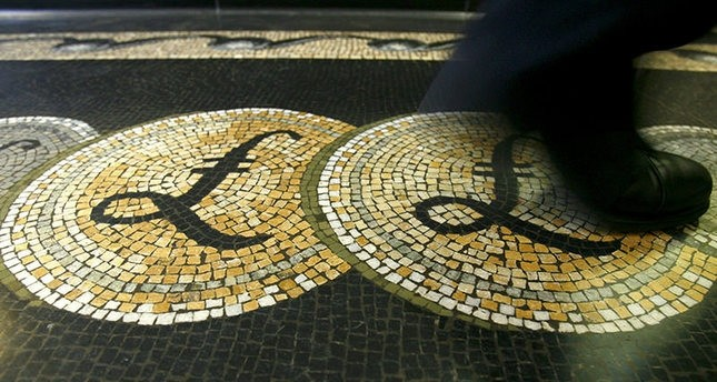 An employee is seen walking over a mosaic of pound sterling symbols set in the floor