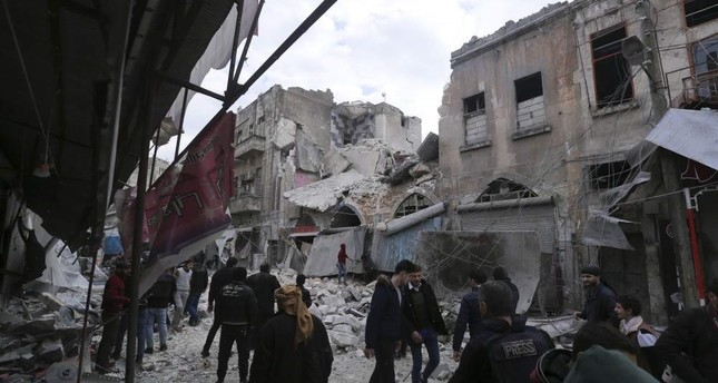 People walk past destruction caused by regime airstrikes in the town of Ariha, Idlib, Jan.15, 2020. AP PHOTO