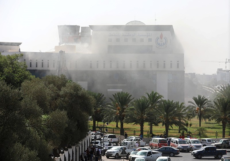 Smoke rises from the headquarters of Libyan state oil firm National Oil Corporation (NOC) after three masked persons attacked it in Tripoli, Libya Sept. 10, 2018. (Reuters Photo)