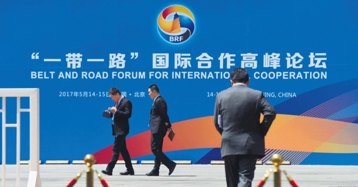 People walk past a billboard for the Belt and Road Initiative (BRI) forum, at the venue for the meeting in Beijing, May 11, 2017.