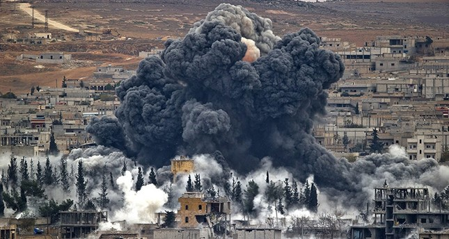 In this Nov. 17, 2014 file photo, smoke rises from the Syrian city of Kobani, following an airstrike by the US led coalition, seen from a hilltop outside Suruc, on the Turkey-Syria border. (AP Photo)