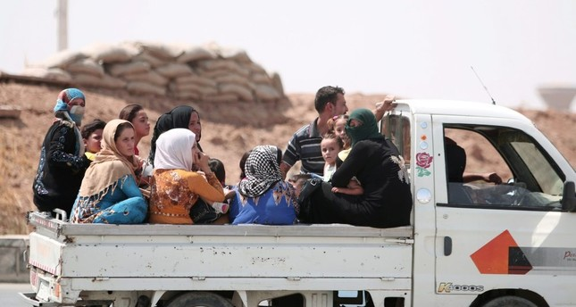 People ride on the back of a pickup truck as they flee Hasakah, Syria, Aug. 20.