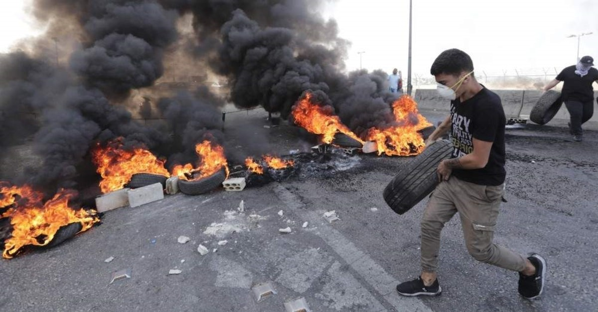 A Lebanese boy moves tires to be burnt to block Beirut's southern entrance, Nov. 13, 2019. (AFP Photo)