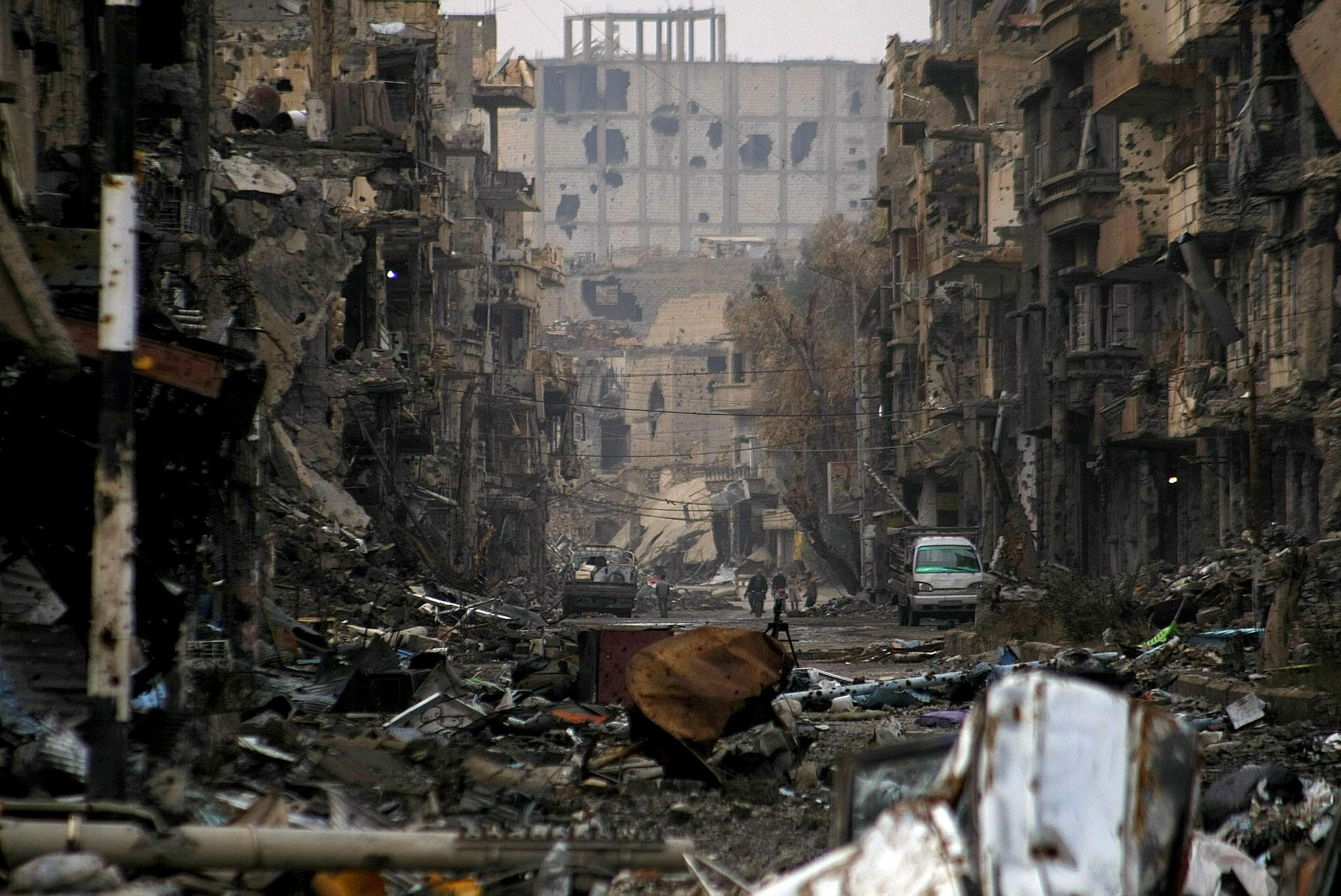 Syrians walk along a severely damaged road in the northeastern Syrian city of Deir al-Zor.