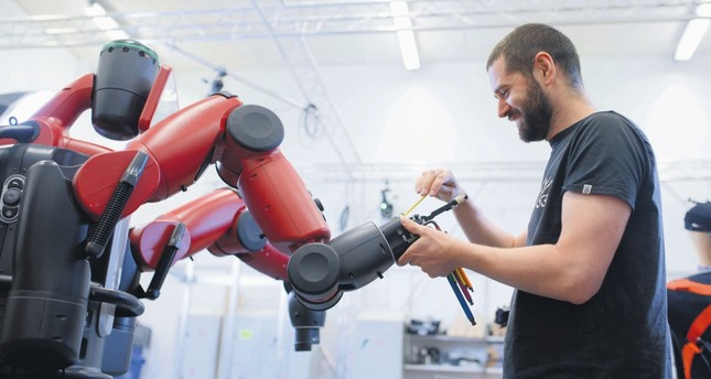 A technician works on a robotic arm. Soon, new jobs will emerge to meet the different needs brought on by technological advances.
