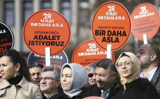 Activists hold placards reading Feb. 28, Never Again, We Want Justice, Not Revenge, outside the Ankara courthouse where defendants accused of the coup are on trial.