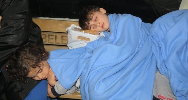 Two children rescued from a migrant boat that sank off the Turkish coast sleep on a bench at the Küçükkuyu port they were taken to in February.