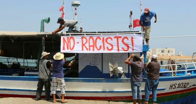 Tunisian fishermen hang banners in the port of Zarzis in southeastern Tunisia, Aug. 6.