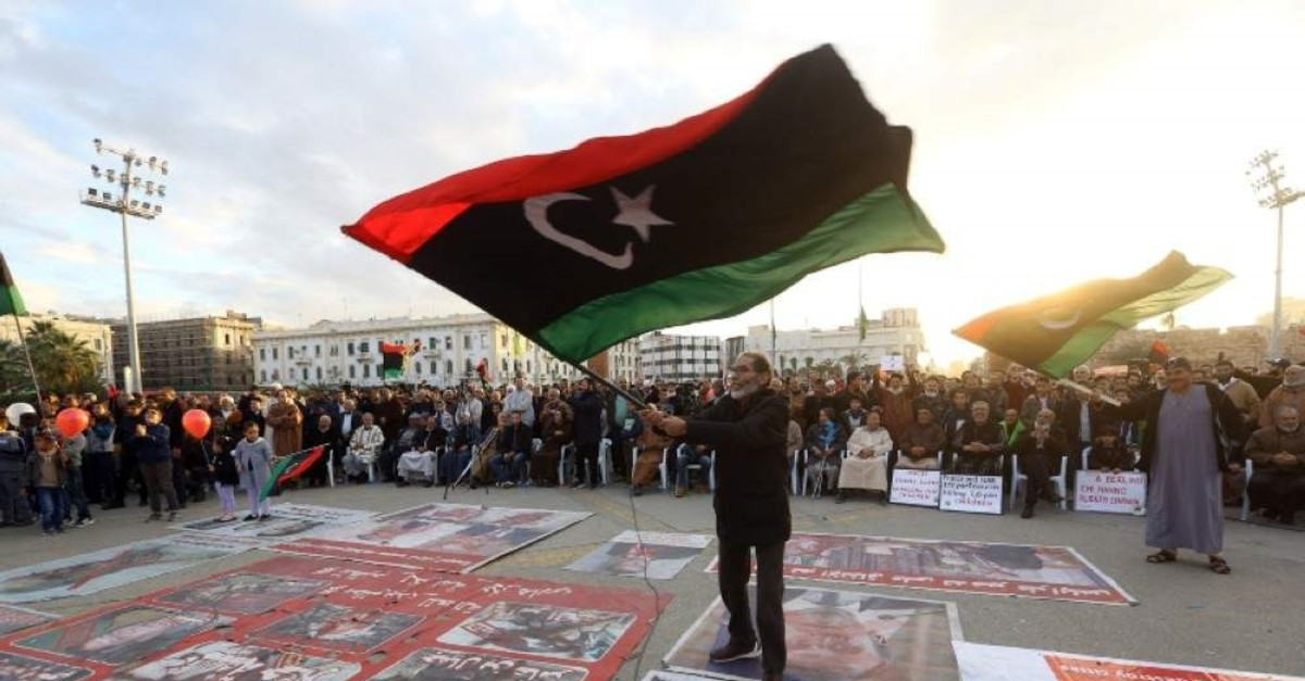 Demonstrators wave flags and step on posters of some world leaders as they take part in a rally against eastern Libyan strongman Khalifa Haftar in Tripoli on Jan. 10, 2020. (AFP Photo)