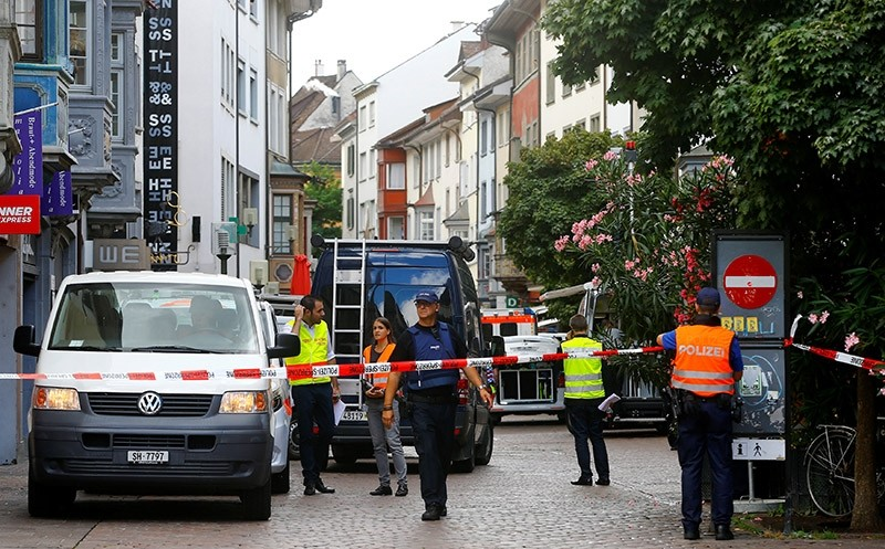 Swiss police officers stand at a crime scene of an alleged chainsaw attack in Schaffhausen, Switzerland July 24, 2017. (Reuters Photo)