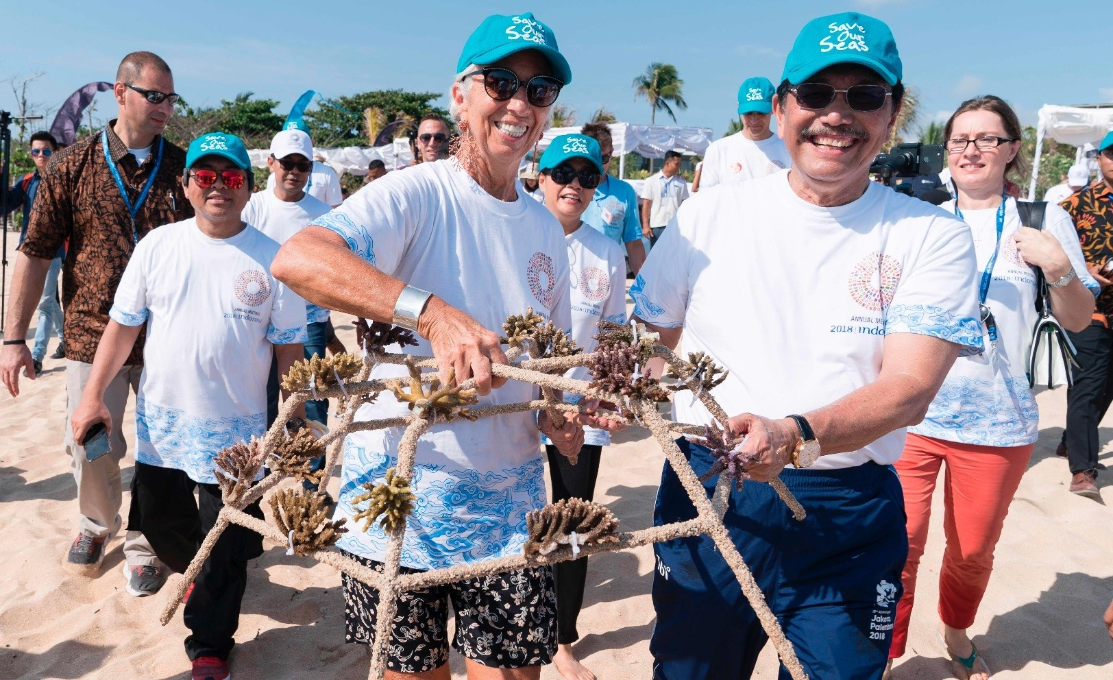 Lagarde (L) and Indonesiau2019s Maritime Affairs Minister Luhut Binsar Pandjaitan carry coral fragments to water where they will help rehabilitate the threatened coral reefs, ahead of the start of the 2018 IMF and World Bank annual meetings in Nusa Dua