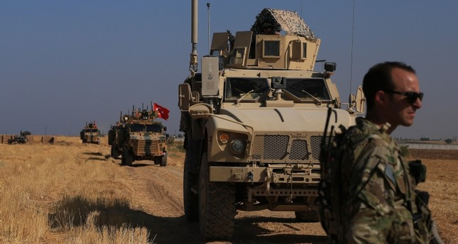 This Friday, Oct. 4, 2019 file photo, Turkish and American armored vehicles patrol as they conduct joint ground patrol in the so-called safe zone on the Syrian side of the border with Turkey, near the town of Tal Abyad (AP Photo)