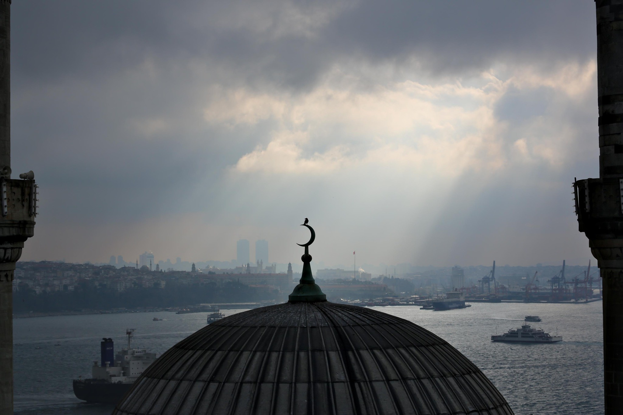 This photo shows a bird standing on the crescent atop the dome of Cihangir Mosque in Istanbul's Beyou011flu district with the Bosporus and Asian side in the background. (Photo: YKKSY/Orhan Pamuk)
