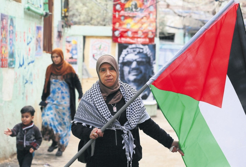 A Palestinian woman carries a Palestinian flag next to posters depicting pictures of late Palestinian president Yasser Arafat, Beirut, Lebanon, Dec. 7.