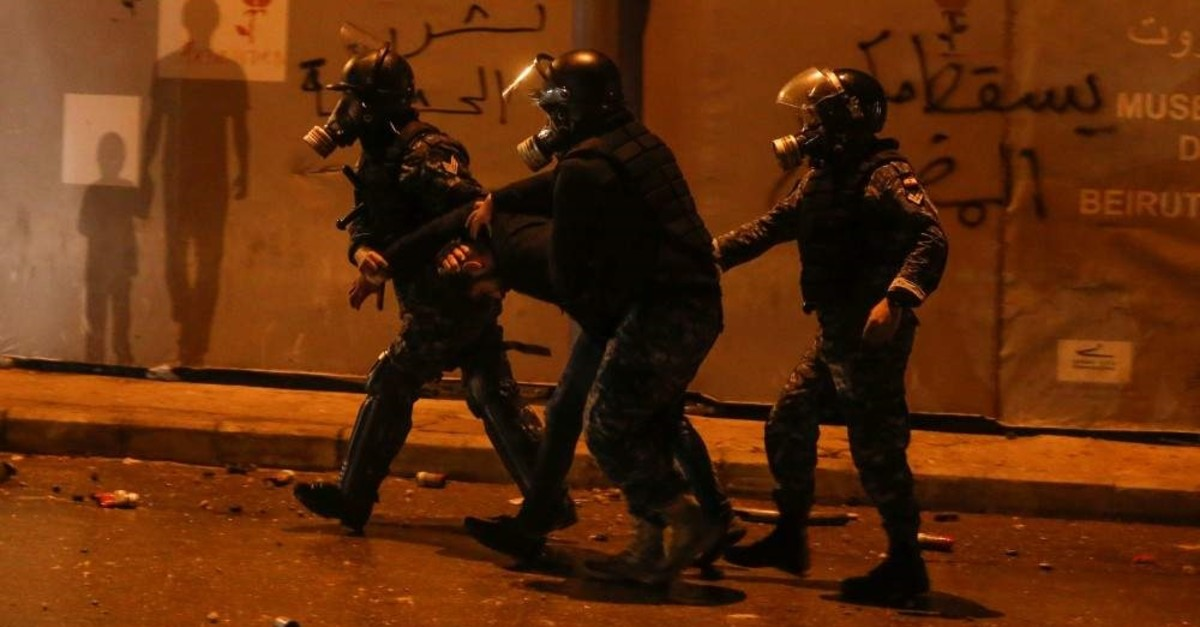 Riot police restrain a protestor during anti-government protests, Beirut, Jan. 18, 2020. (REUTERS Photo)