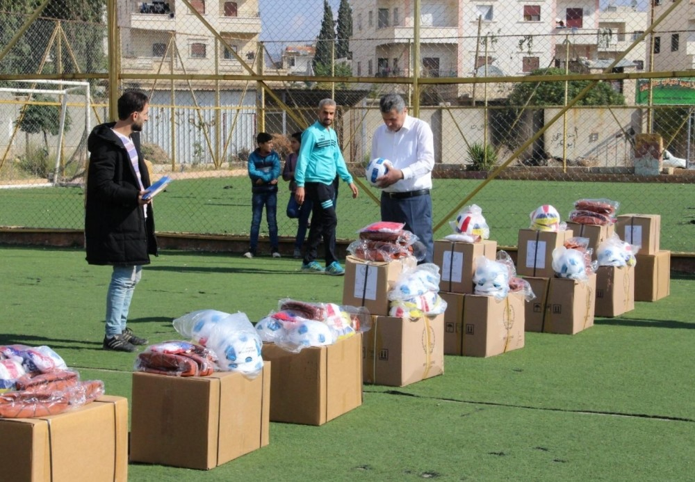 An official from Turkey's southern Hatay province distributes football and table tennis equipment as well as backpacks and jerseys to students in Afrin, Feb. 7, 2019.