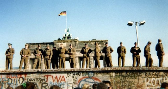 East German border guards stand on a section of the Berlin Wall, with the Brandenburg gate in the background, Berlin, Nov. 11, 1989. AFP