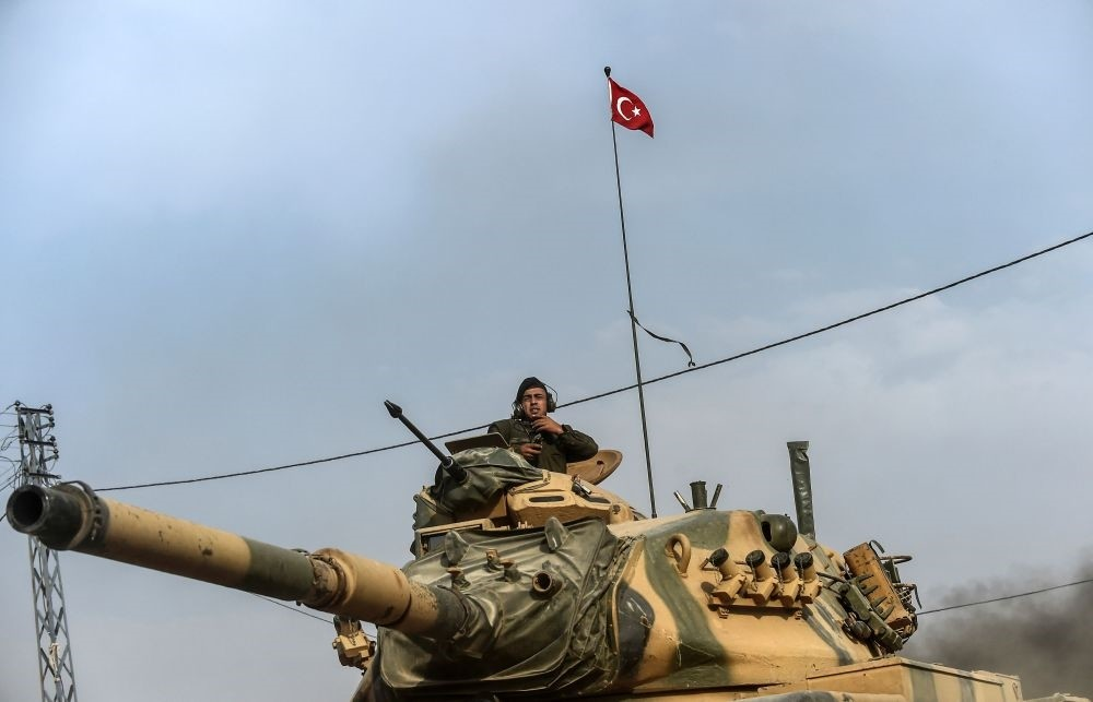 A Turkish soldier gesturing as Turkish Army tanks drive to Syrian Turkish border town of Jarablus as part of Operation Euphrates Shield, which was launched in August 2016 against regional terrorist groups such as Daesh, PKK and PYD, Aug. 25, 2016.