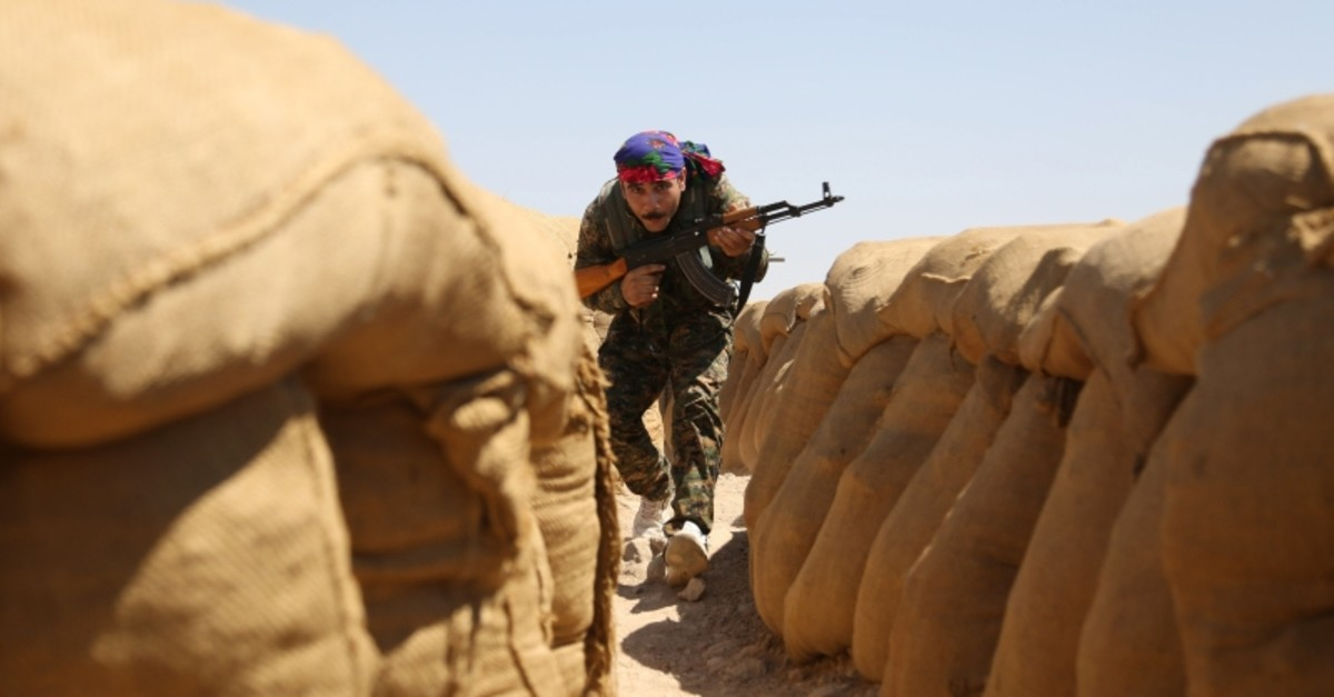 A fighter from the terrorist PKK-linked People's Protection Unit (YPG) walks between sandbags on the front line in the northeastern Syrian city of Hasakeh on September 4, 2015 (Reuters File Photo)