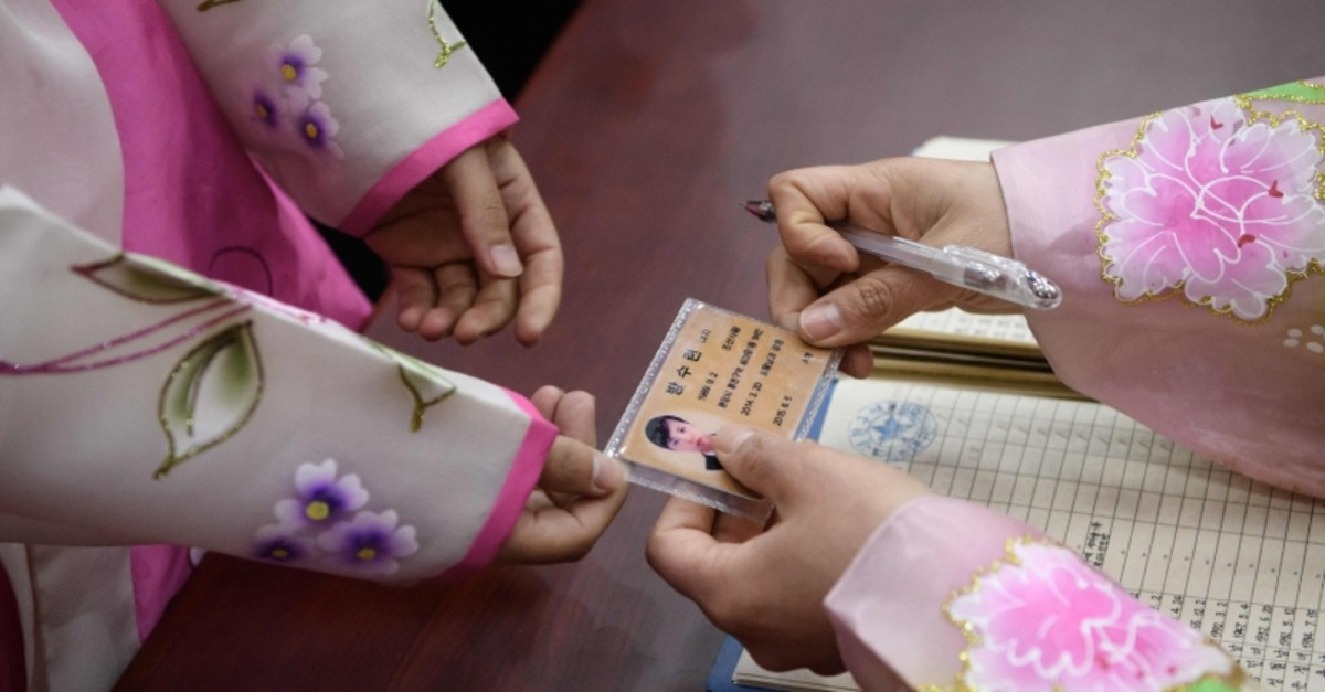 A voter uses an ID card to register to cast their ballot at the '3.26 Pyongyang Cable Factory' during voting for the Supreme People's Assembly elections, in Pyongyang on March 10, 2019 (AFP Photo)
