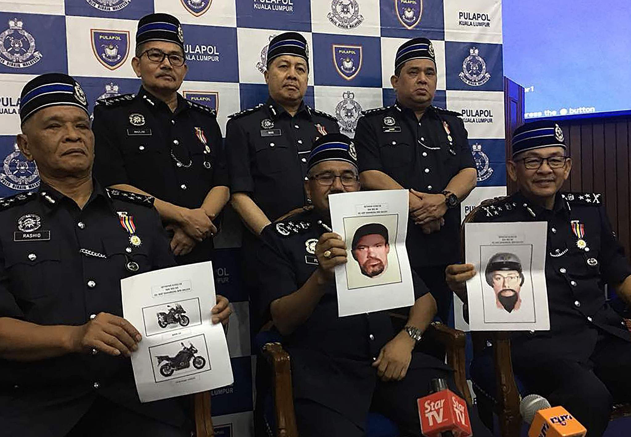 Malaysia Chief Police Mohamad Fuzi Harun (C) with other police officials holding computer-generated images of suspects involved in assassinated a Palestinian scientist in a drive-by shooting in Kuala Lumpur. (AFP Photo)
