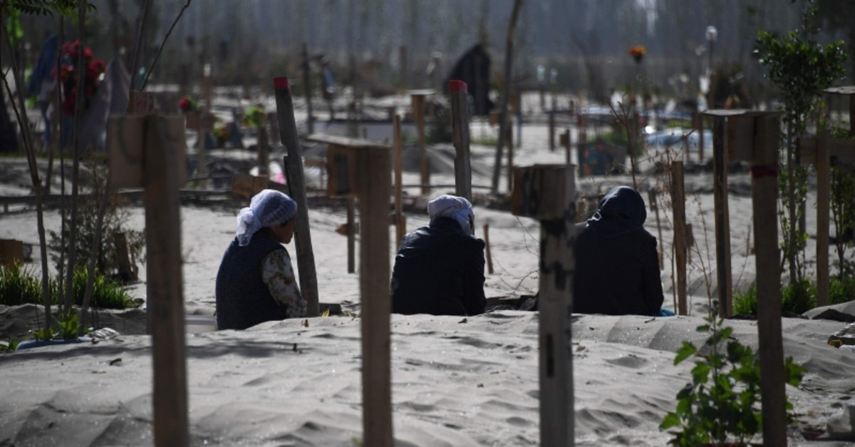 This photo taken on May 31, 2019 shows Uighur women praying in a graveyard on the outskirts of Hotan in China's northwest Xinjiang region (AFP Photo)