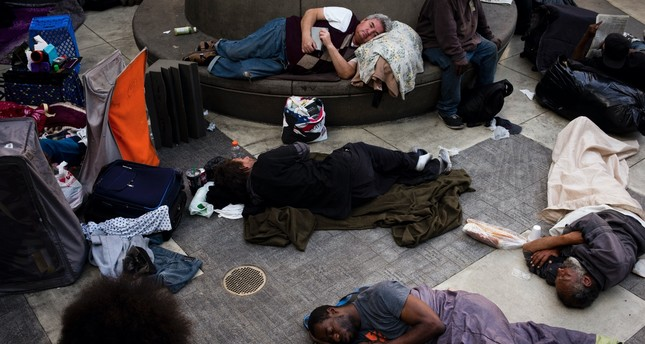 A group of homeless people sleep in the courtyard of the Midnight Mission in Los Angeles. The mission's courtyard is open to all homeless people looking for a safe place to spend the night.