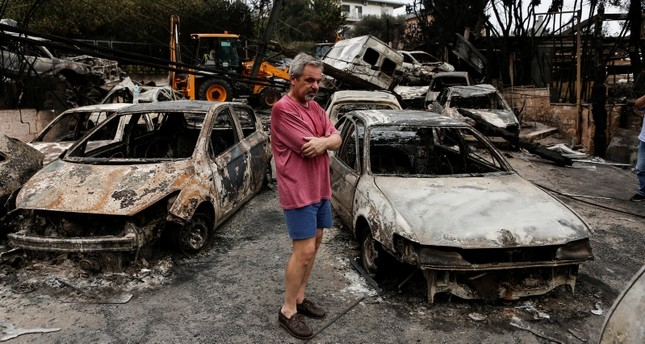 A man pauses as he stands amidst burned cars following a forest fire in Mati a northeast suburb of Athens, Greece, 24 July 2018. (EPA Photo)