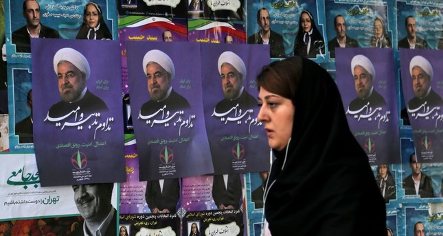 An Iranian woman walks past a wall plastered with election posters of Iranian President and candidate in the upcoming elections, Hassan Rouhani, in capital Tehran on May 18, 2017.