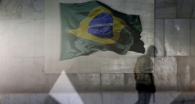 A presidential guard walks past a window allowing a view into the Planalto presidential palace's main lounge, decorated with an image of a Brazilian national flag, in Brasilia.