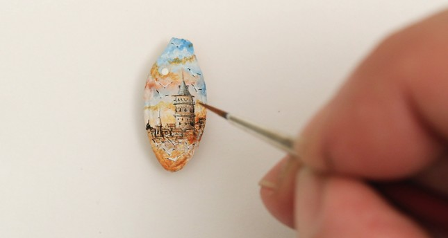 Turkish micro artist Hasan Kale puts the final touches as he paints the Galata Tower on a pumpkin seed.