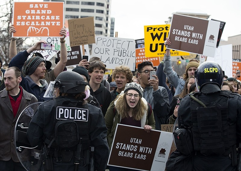 Protesters yell as police stop them from marching up State Street during President Donald Trump's announcement to eliminate vast portions of Utah's conservation areas in Salt Lake City, Utah (AP Photo)