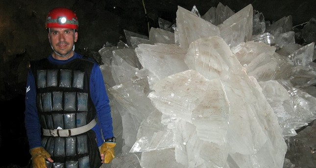 Mike Spilde stands near to a gypsum rosette crystal. (Mike Spilde via AP)