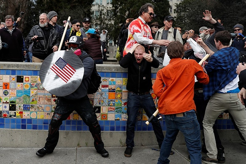 A demonstrator supporting U.S. President Donald Trump (L) holds a shield as a group of men punch a demonstrator during a ,People 4 Trump, rally in Berkeley, California March 4, 2017. (Reuters Photo)