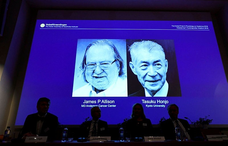 Members of the Nobel Committee for Physiology or Medicine sit in front of a screen displaying James P Allison (L) and Tasuku Honju, the winners of the 2018 Nobel Prize in Physiology or Medicine. (AFP Photo)