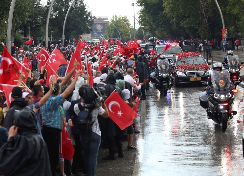Supporters line the streets with Turkish flags as some throw flowers to the car of President Erdoğan on his way the mausoleum of the nation's founding father Mustafa Kemal Atatürk, in Ankara, Turkey, Monday, July 9, 2018.