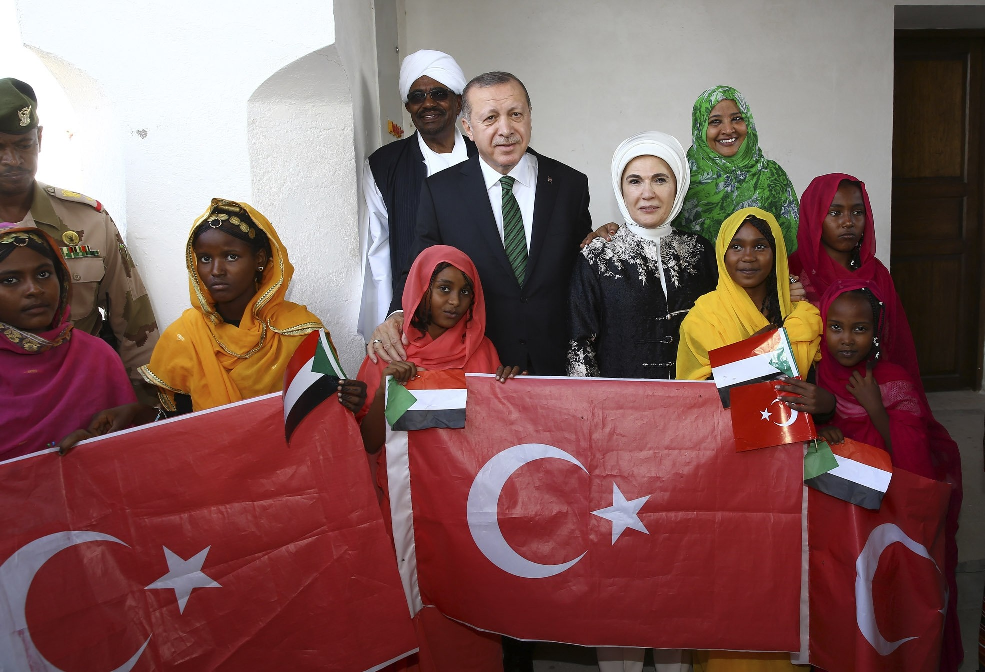 President Erdou011fan (C), accompanied by first lady Emine Erdou011fan, pose for a photograph with Sudan's President Omar al-Bashir and first lady Widad Babiker u00d6mer Modawi alongside local people holding the Sudanese and Turkish flags in Port Sudan, Dec. 25,