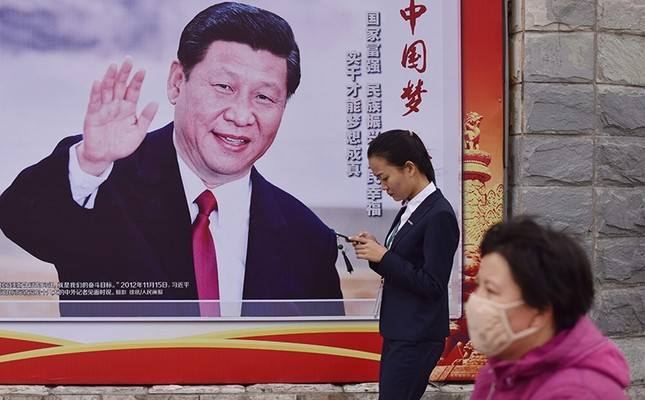 People walk past a poster featuring Chinese President Xi Jinping with a slogan reading Chinese Dream, People's Dream beside a road in Beijing, China, Oct. 16, 2017. (AFP Photo)