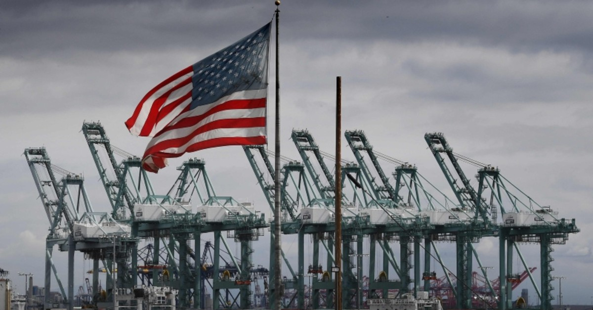 The U.S. flag flies over shipping cranes and containers in Long Beach, California on March 4, 2019. (AP Photo)